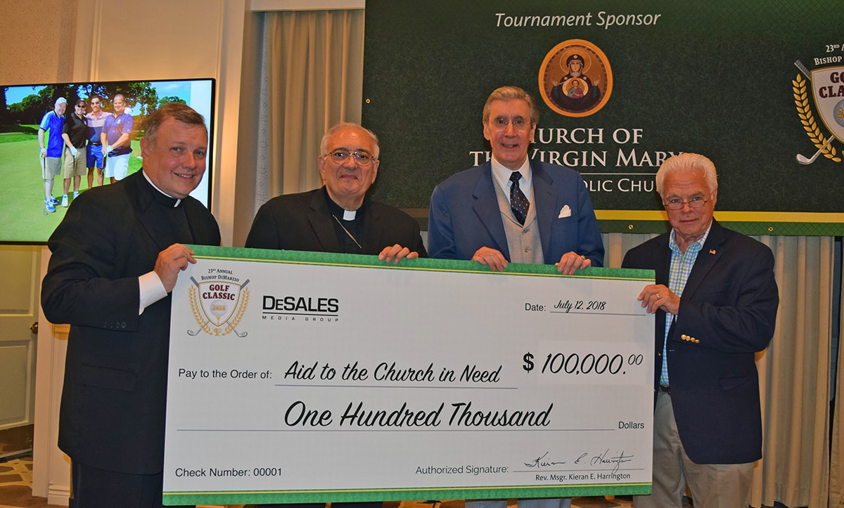 Bishop DiMarzio, a priest and two men holding an oversized check