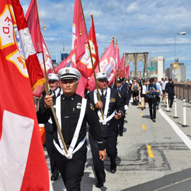 Fire department officials walking inline with flags over Brooklyn Bridge