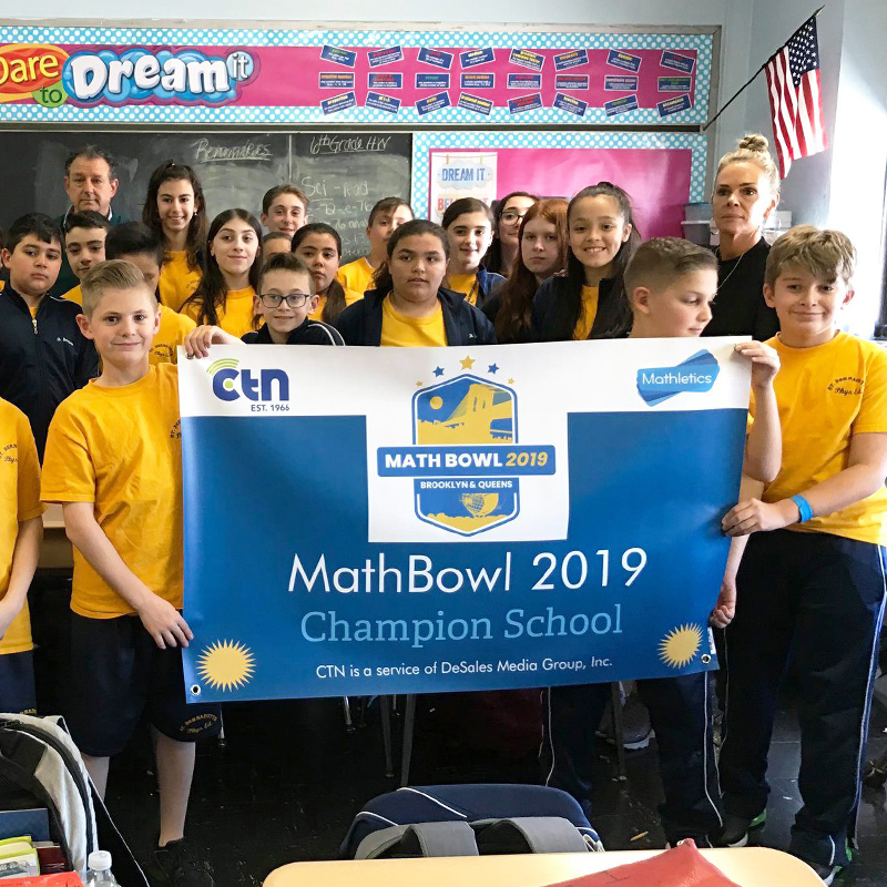 students and teacher in a classroom holing banner for Math Bowl 2019