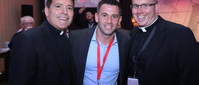 two priests and a man posing for a picture