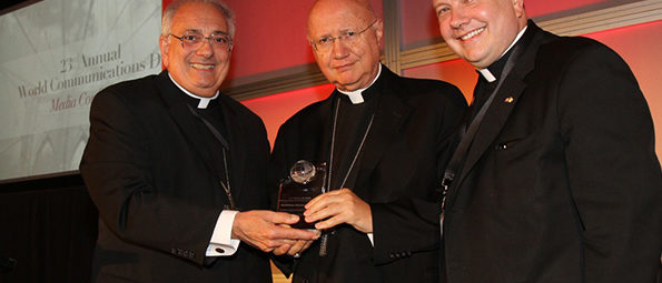 Bishop DiMarzio and two priests holding an award