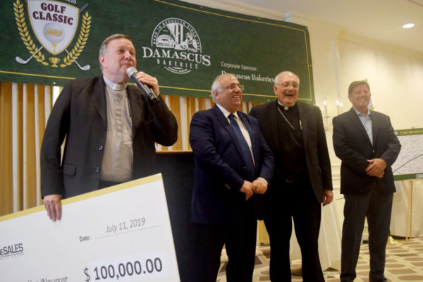 Monsignor Harrington prepares to give Tele Lumiere/Noursat $100,000 check.