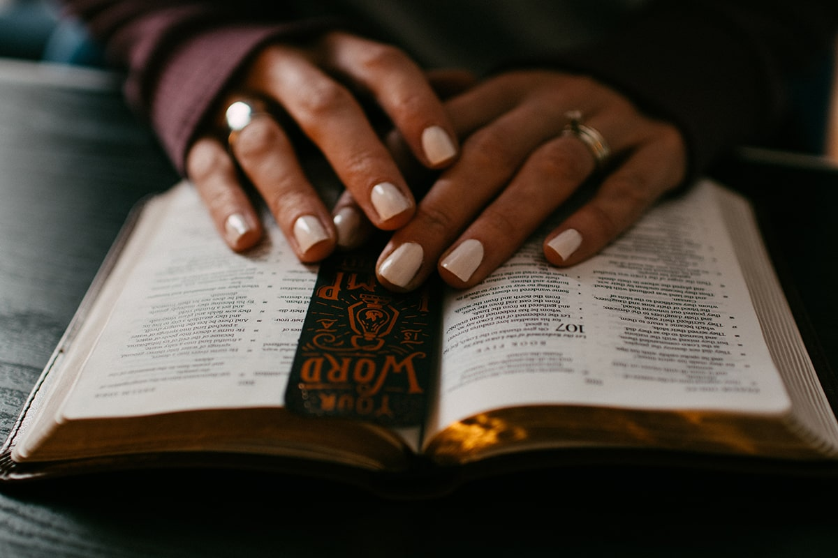 A woman hands on Bible